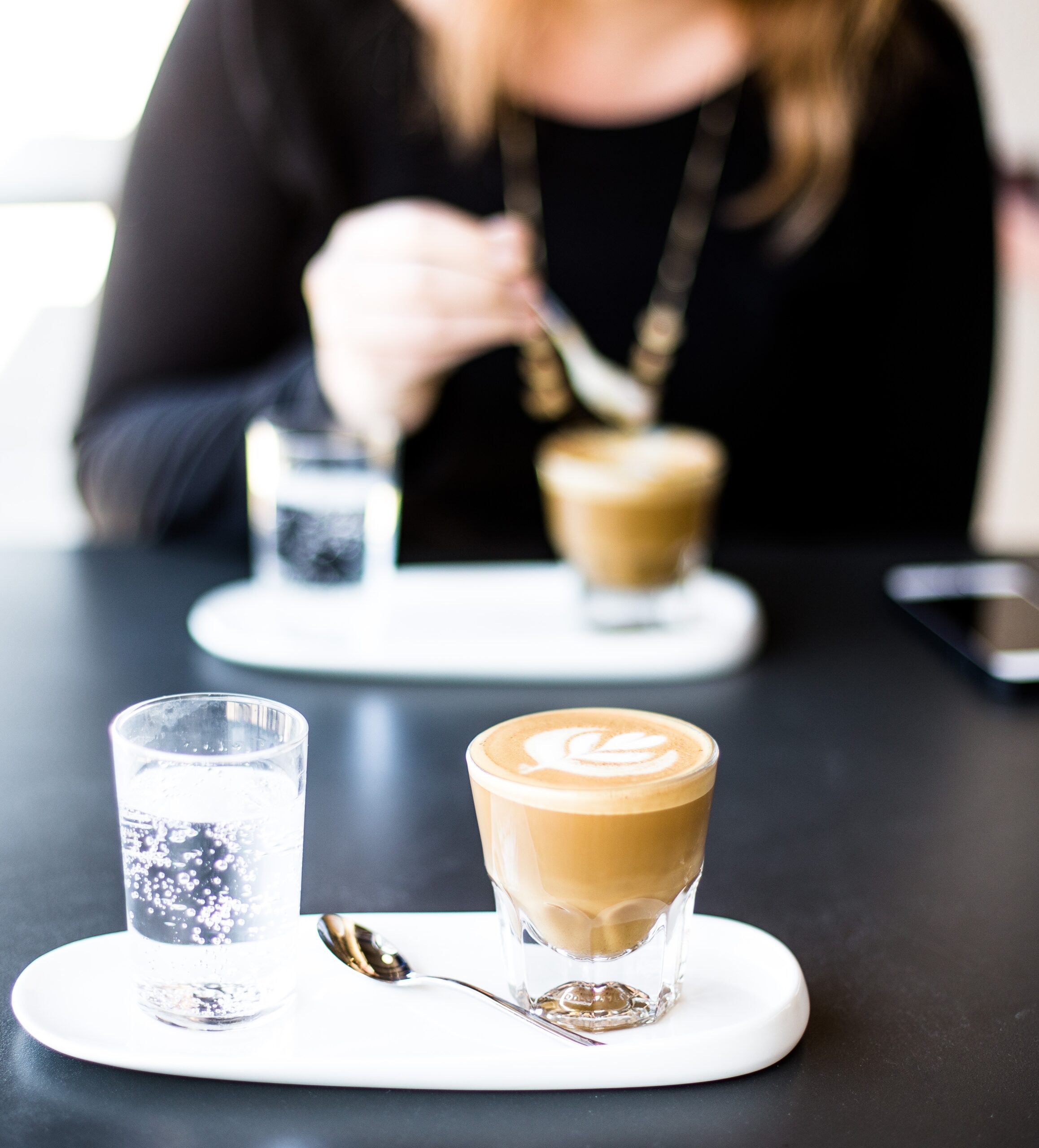 Two individuals having a coaching session around a coffee